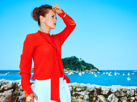 Luxury weekend retreat. modern woman in red blouse standing in front of the beautiful scenery overlooking lagoon with yachts in Donostia; San Sebastian, Spain looking into the distance