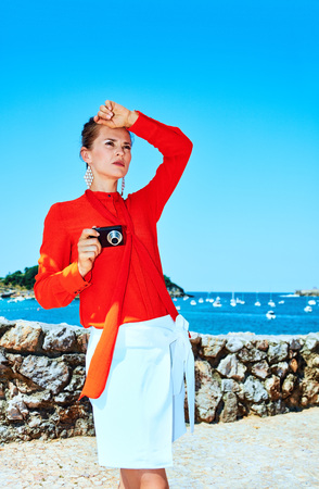 Luxury weekend retreat. young traveller woman in red blouse standing in front of the beautiful scenery overlooking lagoon with yachts in Donostia; San Sebastian, Spain with digital photo camera Stock Photo