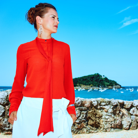 Luxury weekend retreat. Portrait of trendy woman in red blouse standing in front of the beautiful scenery overlooking lagoon with yachts in Donostia; San Sebastian, Spain looking aside