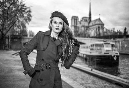 Bright in Paris. Portrait of modern woman in red trench coat standing on embankment in Paris, France