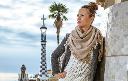 Barcelona signature style. Full length portrait of young woman at Guell Park in Barcelona, Spain in the winter looking into the distance