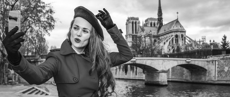 Bright in Paris. cheerful trendy traveller woman in red trench coat on embankment near Notre Dame de Paris in Paris, France with mobile phone taking selfie