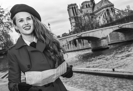 Bright in Paris. smiling elegant tourist woman in red trench coat on embankment near Notre Dame de Paris in Paris, France with map looking into the distance Stock Photo
