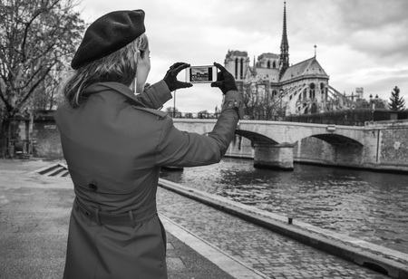 Bright in Paris. Seen from behind trendy traveller woman in red trench coat on embankment near Notre Dame de Paris in Paris, France with phone taking photo