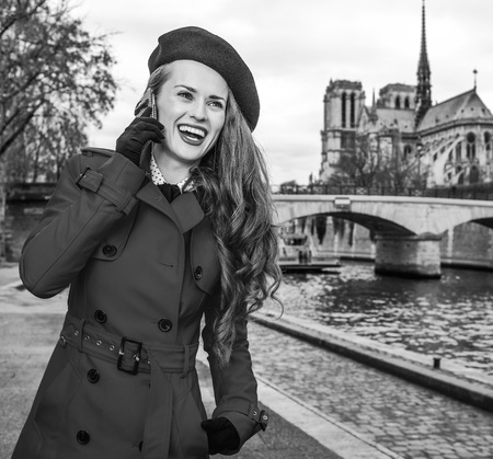 Bright in Paris. happy elegant traveller woman in red trench coat on embankment near Notre Dame de Paris in Paris, France talking on a smartphone
