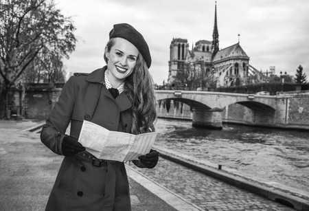 Bright in Paris. smiling trendy traveller woman in red trench coat on embankment in Paris, France with map