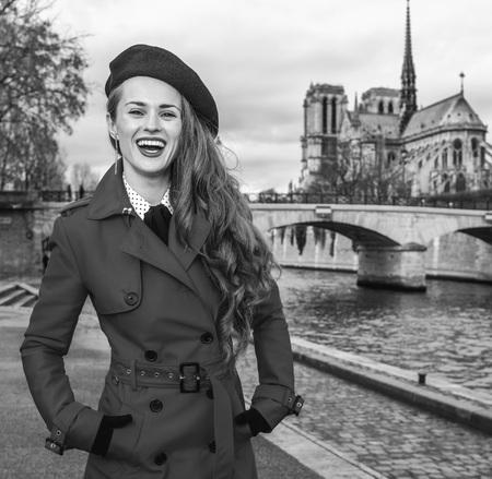 Bright in Paris. Portrait of happy elegant tourist woman in red trench coat on embankment near Notre Dame de Paris in Paris, France