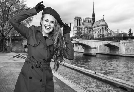Bright in Paris. Portrait of smiling modern woman in red trench coat on embankment in Paris, France having fun time