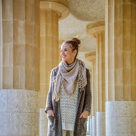 Barcelona signature style. Full length portrait of happy young tourist woman  at Guell Park in Barcelona, Spain in the winter enjoying promenade