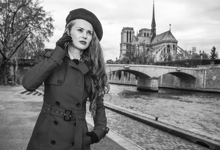 Bright in Paris. elegant traveller woman in red trench coat on embankment near Notre Dame de Paris in Paris, France talking on a smartphone