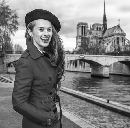 Bright in Paris. happy trendy tourist woman in red trench coat on embankment near Notre Dame de Paris in Paris, France having walking tour