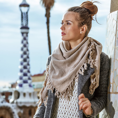 Barcelona signature style. Portrait of trendy tourist woman at Guell Park in Barcelona, Spain in the winter looking aside