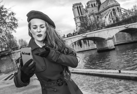 Bright in Paris. smiling young tourist woman in red trench coat on embankment near Notre Dame de Paris in Paris, France with phone taking selfie Stock Photo
