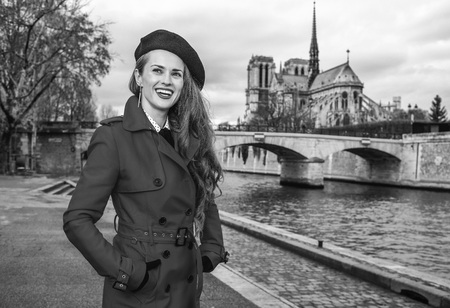 Bright in Paris. smiling elegant traveller woman in red trench coat on embankment in Paris, France looking into the distance