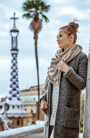 Barcelona signature style. smiling young tourist woman at Guell Park in Barcelona, Spain in the winter looking into the distance