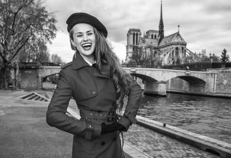 Bright in Paris. cheerful young tourist woman in red trench coat on embankment in Paris, France Stock Photo