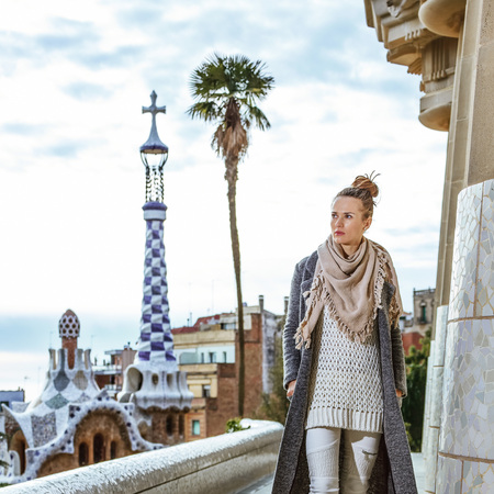 Barcelona signature style. Full length portrait of young tourist woman at Guell Park in Barcelona, Spain in the winter having walking tour