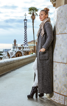 Barcelona signature style. Full length portrait of pensive modern tourist woman at Guell Park in Barcelona, Spain in the winter looking into the distance 版權商用圖片