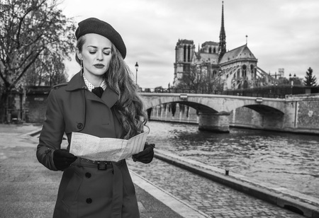 Bright in Paris. young traveller woman in red trench coat on embankment near Notre Dame de Paris in Paris, France looking at the map