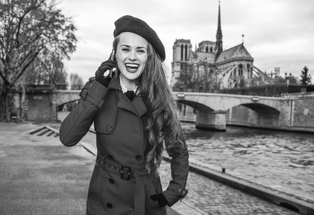 Bright in Paris. Portrait of happy trendy woman in red trench coat on embankment in Paris, France talking on a cell phone