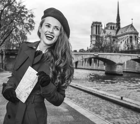 Bright in Paris. smiling trendy tourist woman in red trench coat on embankment near Notre Dame de Paris in Paris, France with map