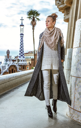 Barcelona signature style. Full length portrait of trendy woman  at Guell Park in Barcelona, Spain in the winter walking