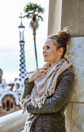 Barcelona signature style. stylish woman standing near column at Guell Park in Barcelona, Spain in the winter