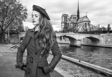 Bright in Paris. elegant traveller woman in red trench coat on embankment near Notre Dame de Paris in Paris, France