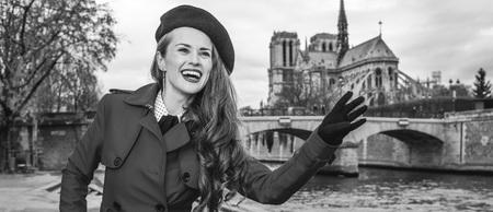 Bright in Paris. smiling trendy traveller woman in red trench coat on embankment in Paris, France handwaving
