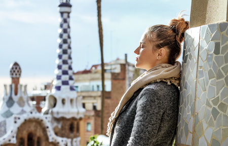 Barcelona signature style. Portrait of relaxed young traveller woman at Guell Park in Barcelona, Spain in the winter