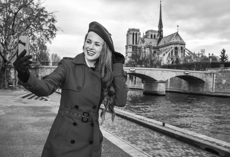 Bright in Paris. happy trendy tourist woman in red trench coat on embankment in Paris, France with cellphone taking selfie Stock Photo