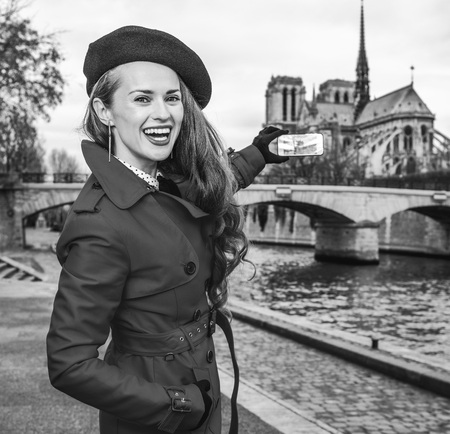 Bright in Paris. happy trendy woman in red trench coat on embankment near Notre Dame de Paris in Paris, France with mobile phone taking photo