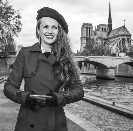 Bright in Paris. smiling young tourist woman in red trench coat on embankment in Paris, France writing sms