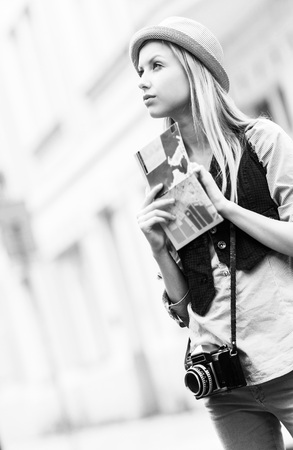 Young woman tourist with map in the city