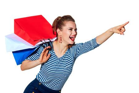 french way: Shopping. The French way. smiling stylish woman with shopping bags of the colours of the French flag isolated on white background pointing at something