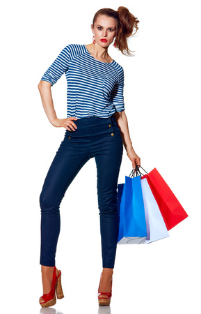 french way: Shopping. The French way. Full length portrait of stylish fashion-monger with shopping bags of the colours of the French flag standing isolated on white background