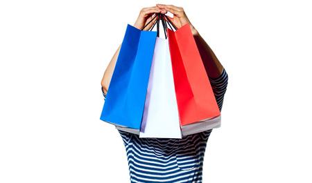 ショッピング。フランスの方法です。若いファッション屋白で隔離フランスの国旗の色の頭の買い物袋の前部を保持しているの完全な長さの肖像画