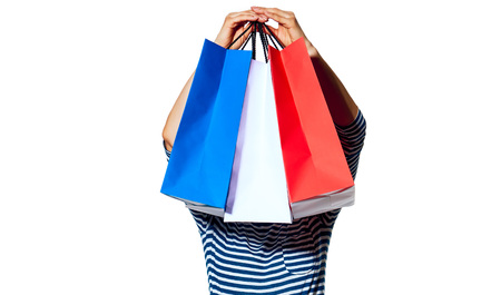 Shopping. The French way. Full length portrait of young fashion-monger holding in the front of head shopping bags of the colours of the French flag isolated on white Reklamní fotografie