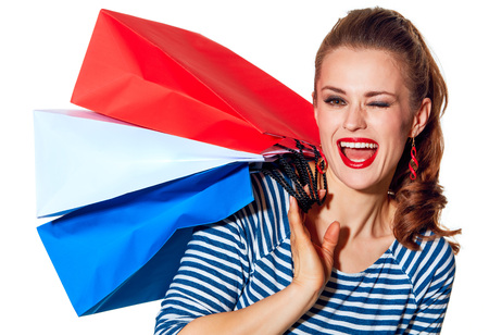norway flag: Shopping. The French way. Portrait of happy stylish fashion-monger with shopping bags of the colours of the French flag isolated on white background winking