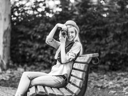 Young hipster taking photo with retro photo camera sitting on bench in the park Stock Photo