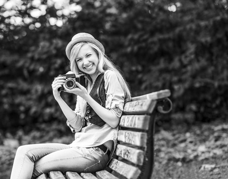 Smiling hipster girl with retro photo camera sitting on bench in the park Stock Photo