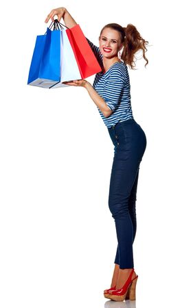 Shopping. The French way. Full length portrait of happy stylish fashion-monger showing shopping bags of the colours of the French flag isolated on white