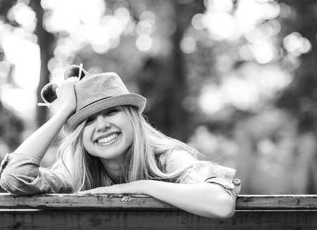 Smiling hipster girl sitting on bench in the park