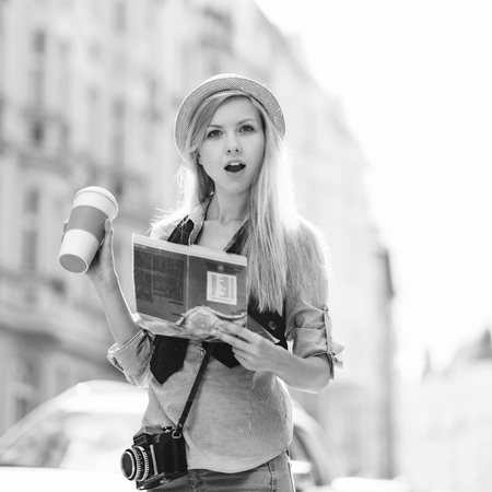 Surprised young woman tourist with map in the city Stock Photo