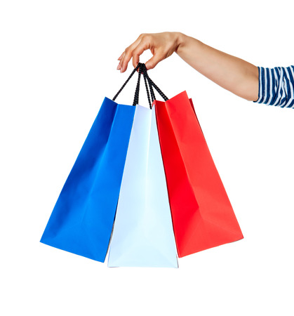 Shopping. The French way. Closeup on hands with shopping bags of the colours of the French flag isolated on white background