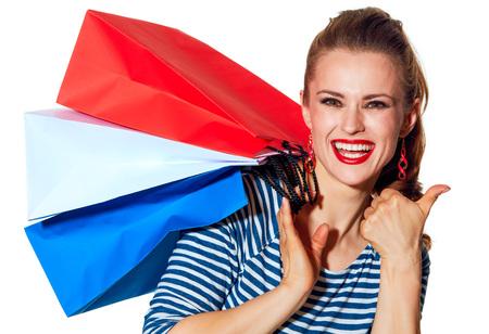 Einkaufen. Der französische Weg Porträt des lächelnden modischen Modehändlers mit Einkaufstaschen der Farben der französischen Flagge lokalisiert auf dem weißen Hintergrund, der sich Daumen zeigt Standard-Bild - 76778871