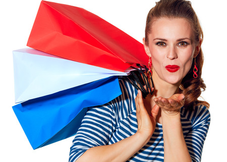 Shopping. The French way. Portrait of happy young woman with shopping bags of the colours of the French flag isolated on white background blowing air kiss