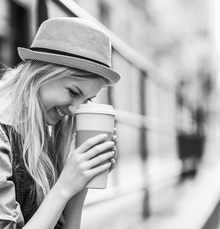 Smiling hipster girl with cup of hot beverage on city street Stock Photo