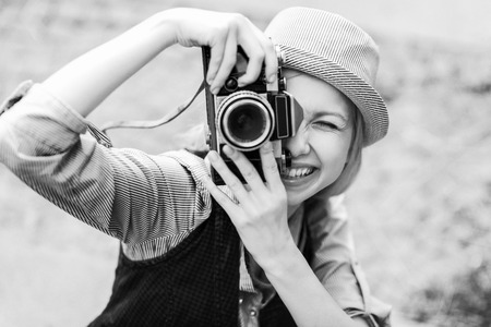Smiling hipster girl making photo with retro camera