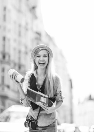 Happy tourist girl with map and cup of hot beverage on city street Stock Photo